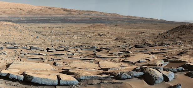 "A view from the ""Kimberley"" formation on Mars taken by NASA's Curiosity rover. The strata in the foreground dip towards the base of Mount Sharp, indicating flow of water toward a basin that existed before the larger bulk of the mountain formed. The colours are adjusted so that rocks look approximately as they would if they were on Earth, to help geologists interpret the rocks. Image Credit: NASA/JPL-Caltech/MSSS"