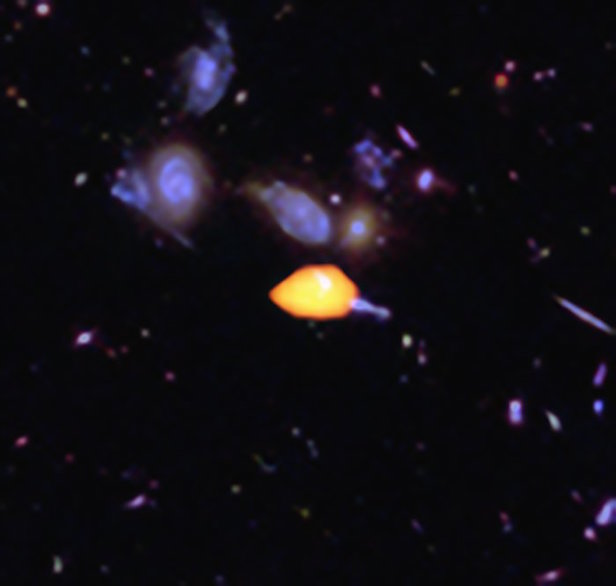ALMA surveyed the Hubble Ultra Deep Field, uncovering new details of the star-forming history of the Universe. This close-up image reveals one such galaxy (orange), rich in carbon monoxide, showing it is primed for star formation. The blue features are galaxies imaged by Hubble. Image Credit: NRAO/AUI/NSF; ESO/NAOJ/NRAO; NASA/ESA Hubble